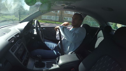 Interior view of a man putting his seat belt on and driving away