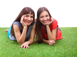 Two young women lying on green grass