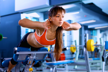 Sports young woman doing exercises on trainer back machine in