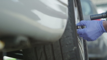 Car mechanic removing a tyre in slow motion