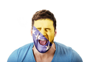 Man with Bosnia and Herzegovina flag on face.