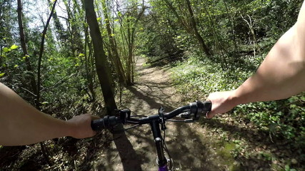 FPV of biker riding through woods on a bright day
