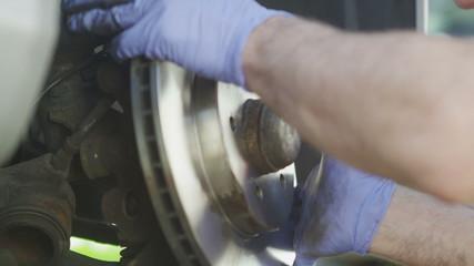 Car mechanic installing a new brake disc