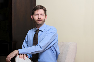 Business man with beard seated with hands on legs