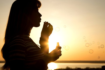 beautiful young girl blow bubbles on nature