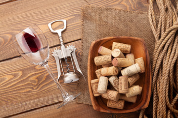 Red wine glass, corkscrew and bowl with corks