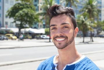 Lachender junger Mann an einer Strasse mit Palmen
