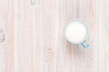 Cup of milk on white wooden table