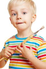 Kind malt Bild mit Pinsel