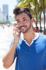 Modischer junger Mann an der Avenida Atlantica am Telefon