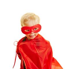 Kind spielt Superheld mit roter Maske