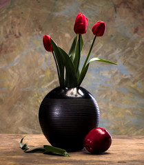 Tulips in a vase and an apple