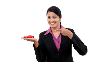Happy young business woman holding toy car