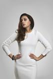 Beautiful brunette girl in white dress against white background