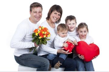Glückliche fünfköpfige Familie mit Herz und Blumenstrauß