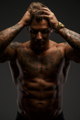 Muscular guy looking down on grey background