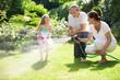Mädchen, Vater und Oma spielen mit Gartenschlauch - 81801555