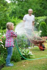 Mädchen spielt mit Gartenschlauch