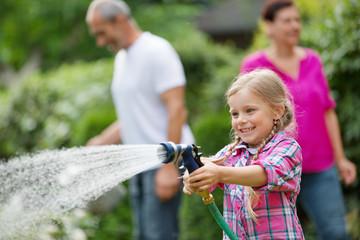 Mädchen mit Gartenschlauch hat Spaß im Garten