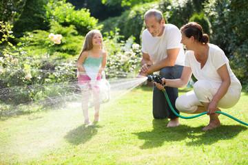 Mädchen, Vater und Oma spielen mit Gartenschlauch