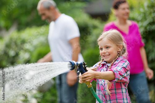 Leinwanddruck Bild Mädchen mit Gartenschlauch hat Spaß im Garten