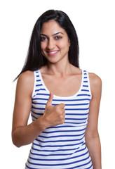 Lachende türkische Frau im gestreiften Shirt zeigt Daumen