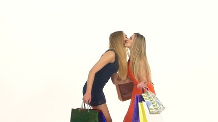 Unexpected meeting of two attractive girls with shopping bags