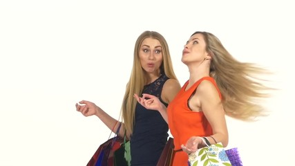 Two attractive girls friends going shopping with bags and
