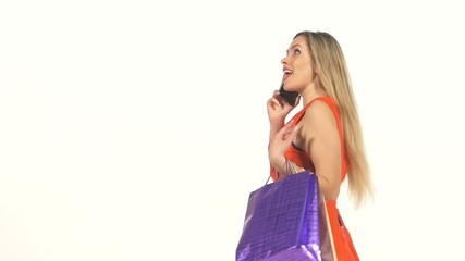 Beautiful woman in red dress with shopping bags talking on the
