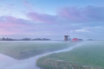 Dutch windmill at misty sunrise
