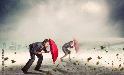 Businessman and businesswoman in storm - 81802914