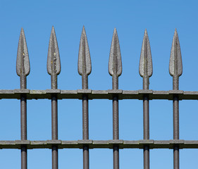 Old wrought iron fence with blue sky