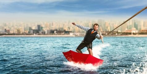 Businessman on water skis in umbrella
