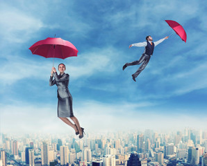 People flying in the sky with umbrellas