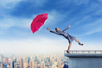 Businessoman standing on th edge with umbrella
