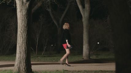 Beautiful girl in high heels walking along a dark park followed