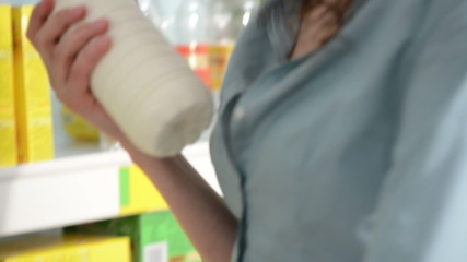 Woman taking a bottle of milk from shelf at supermarket and push
