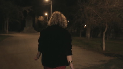 Young woman returns home through the dark park, begins to run