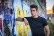 Attractive young man standing against colorful graffiti wall