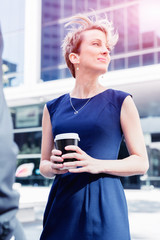 Businesswoman with coffee in a city