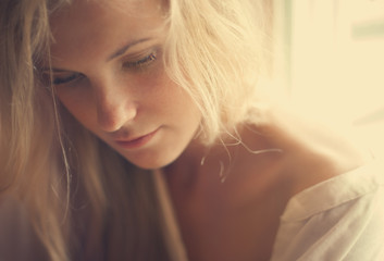 portrait of a beautiful blonde at home by the window