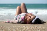 Fototapety Brunette woman lying on the beach, relaxing