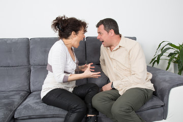Couple screaming at each other on sofa