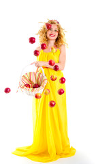 The beautiful girl dressed in yellow is throwing red apples