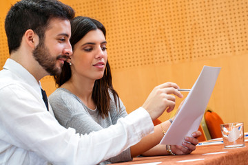 Young business couple reviewing documents in conference hall.