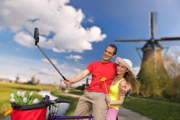 Couple taking Selfie against windmills near Amsterdam, Holland