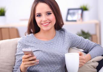 Smiling woman sitting on sofa holding coffee using phone