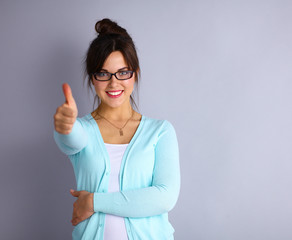 young brunette showing big thumbs up on white background