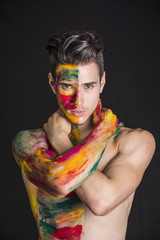 Attractive young man shirtless, skin painted all over with