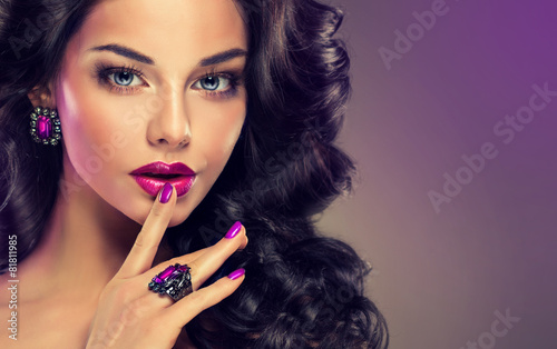 Model curly hair and jewelry , violet makeup , manicure on nails
